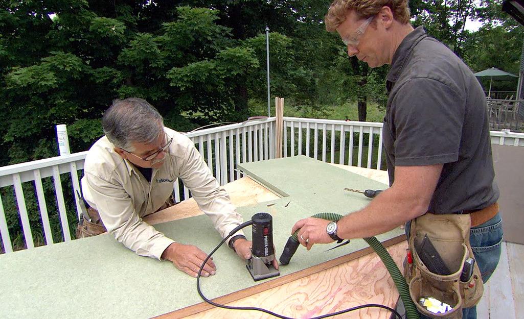 Two men work to create a custom laminate countertop.