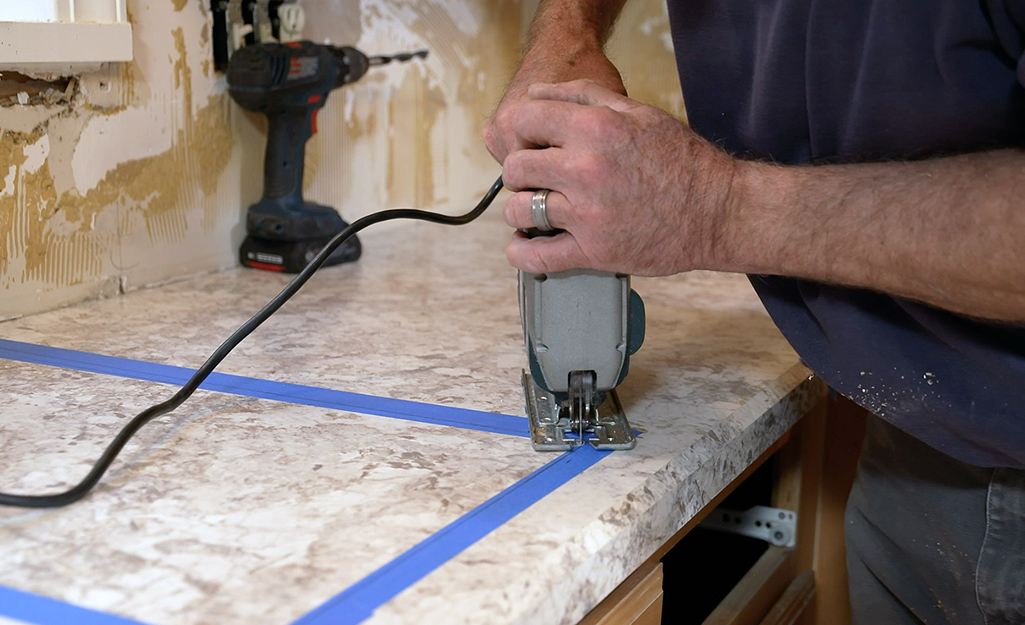 A saw is used to cut a hole in laminate for a sink.