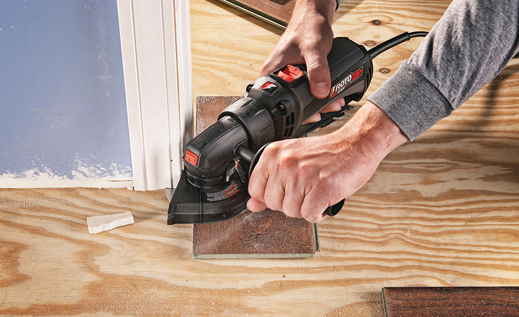 A man uses a saw to prepare door jambs for new flooring.