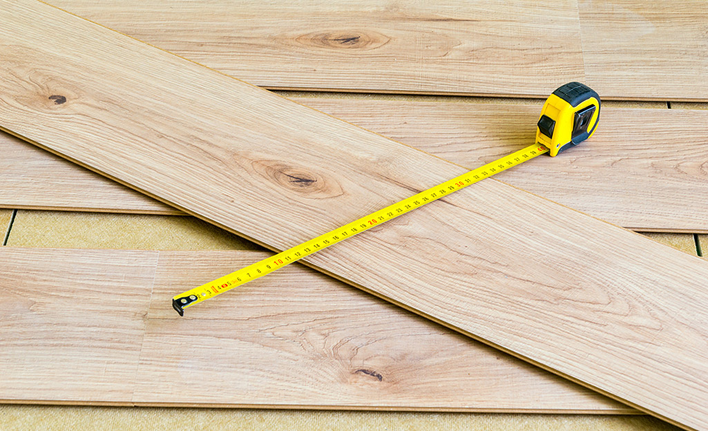 A measuring tape and laminate planks are laid out on a floor.