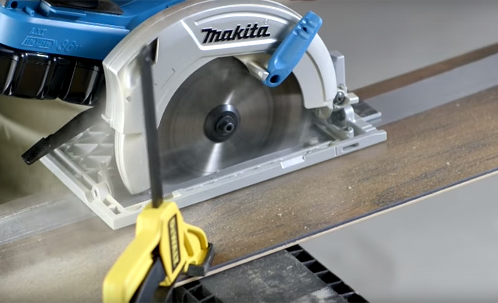A person uses a saw to cut the planks for their flooring.