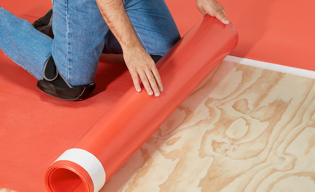 A man wears knee pads to lay down underlayment.
