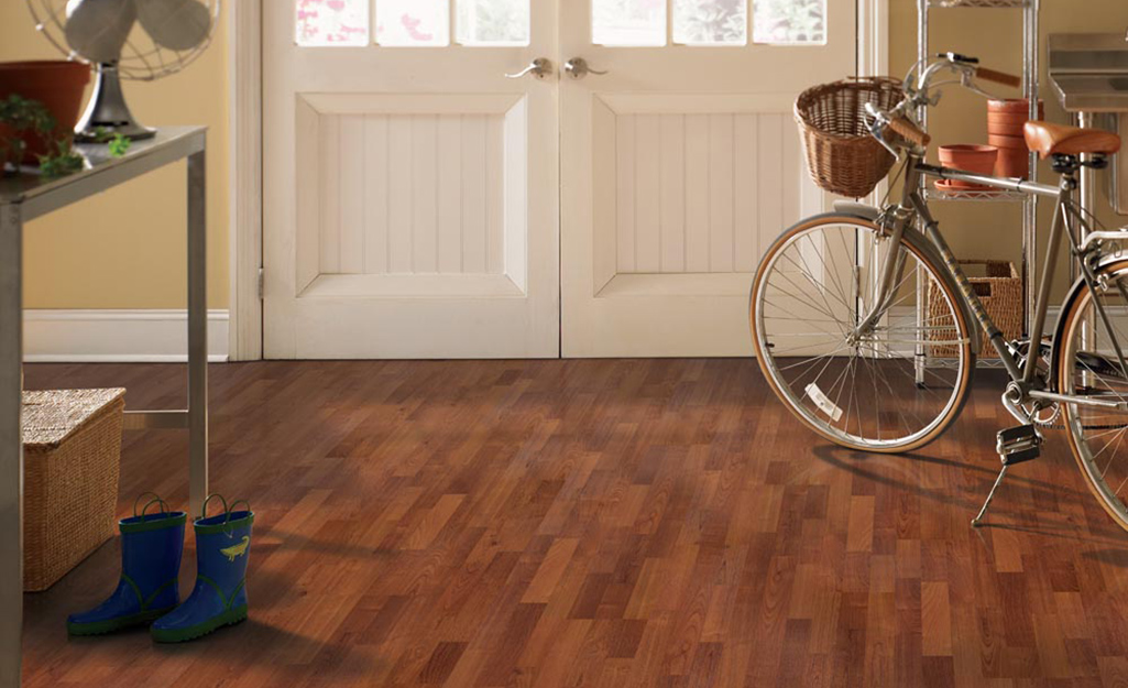 A bicycle sits in a row with laminate flooring.