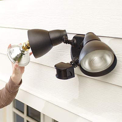 a person screws a bulb into an outdoor floodlight with a motion sensor