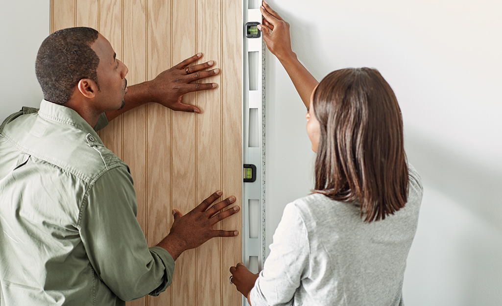 Couple holding level vertically against a sheet of paneling