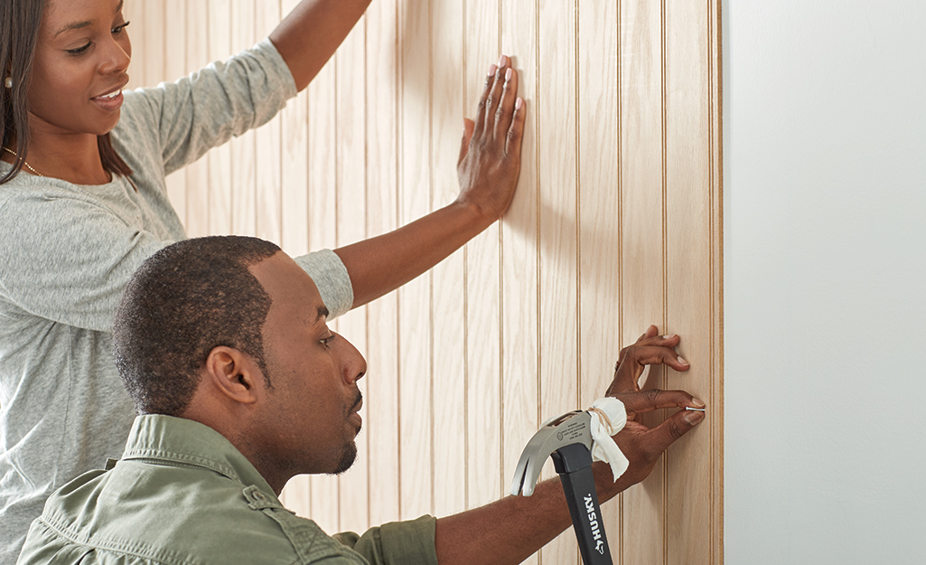 Woman holding paneling while man hammers in finishing nails