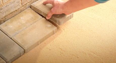 A person placing a cut paver stone.