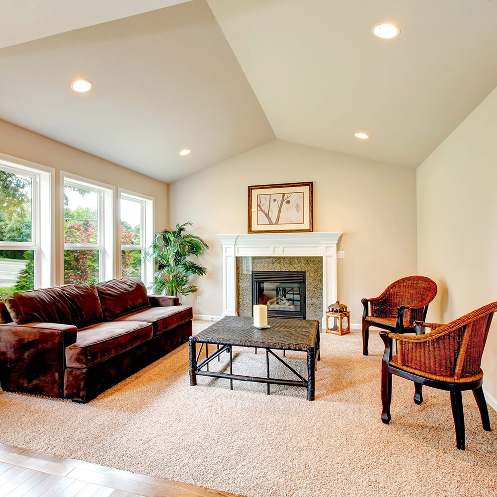 A living room features recessed lighting installed in a sloped ceiling.