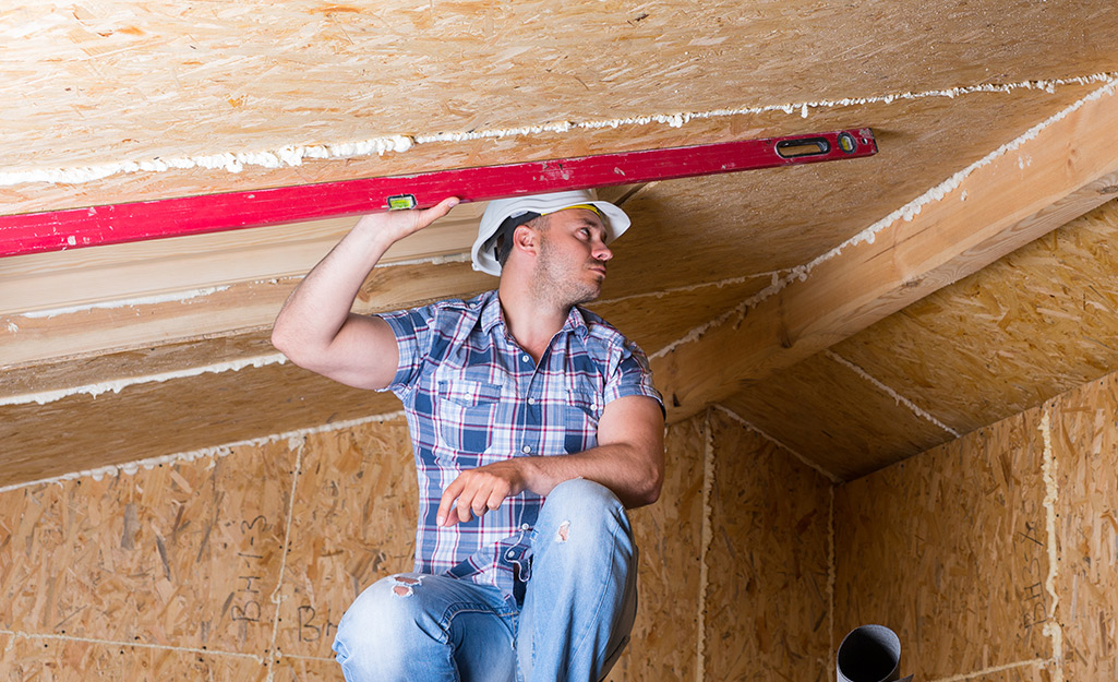 A person takes the measurement of a sloped ceiling.