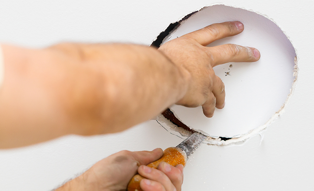 A person cuts a hole in a ceiling with a drywall saw.