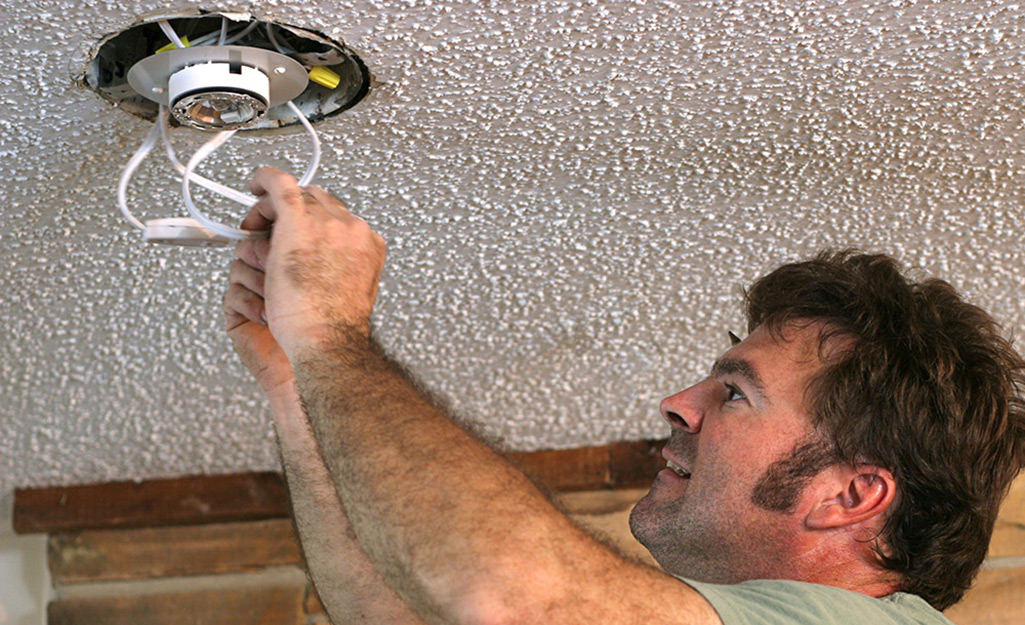 A person installs wiring in the ceiling for recessed lighting.