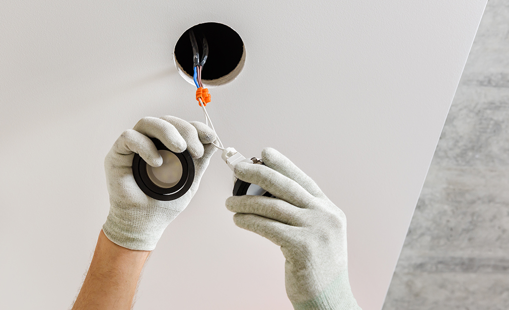 A person prepares to place a recessed light fixture into a vaulted ceiling.