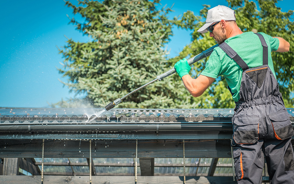 Man preps and cleans a roof.