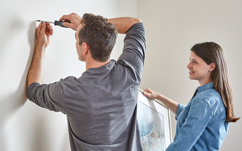 A man and woman removing artwork and nails from a wall.