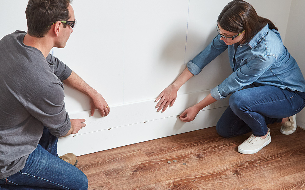 Couple using nickels to space shiplap boards apart on a wall.