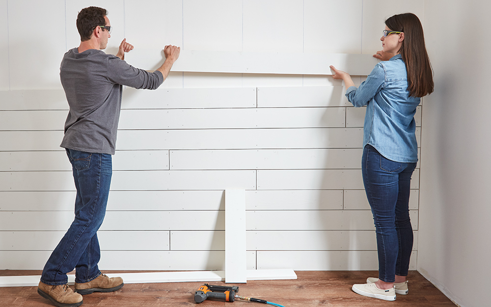 Couple adding shiplap board to a wall that's almost complete.