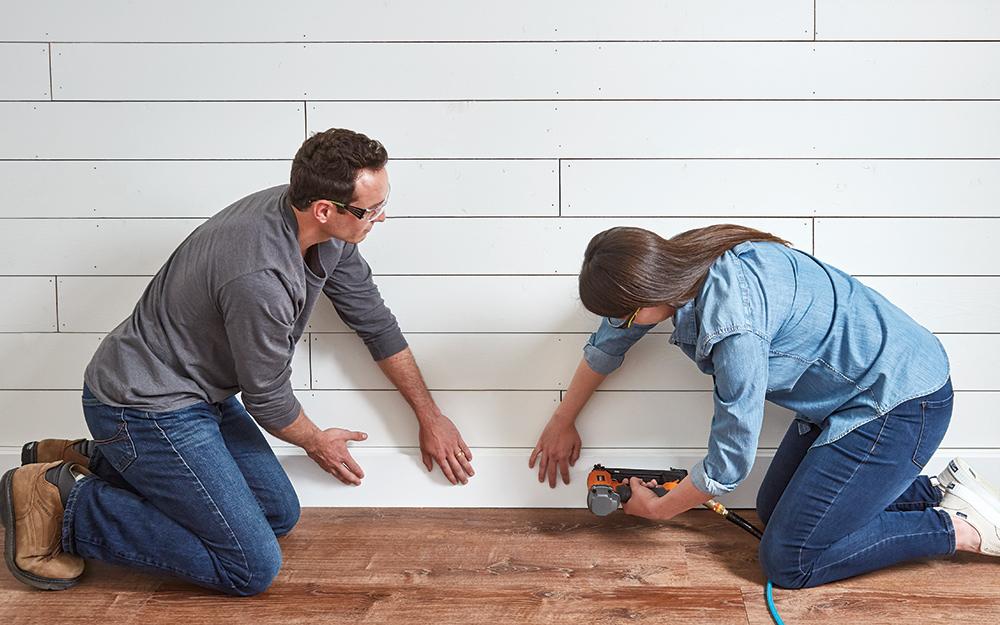 Couple nailing the baseboard along the bottom of the shiplap wall.