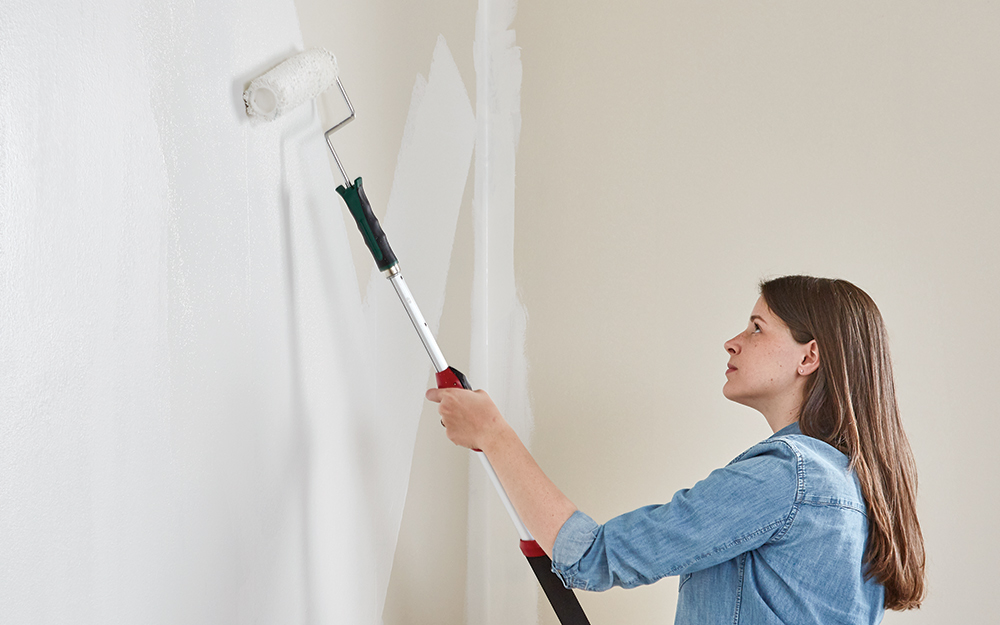 Woman painting wall with a roller.