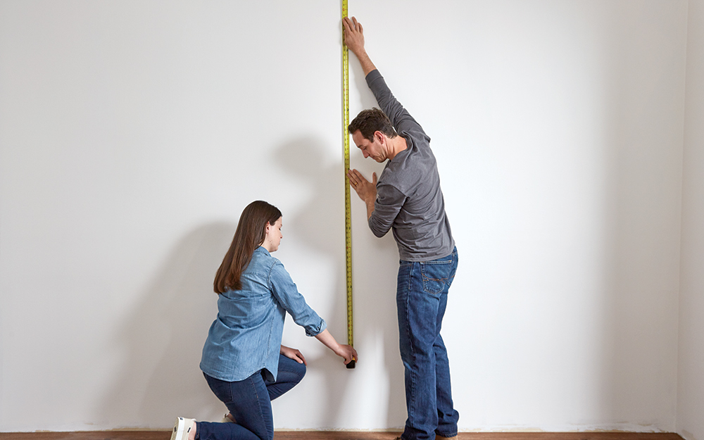 Couple using a tape measure to measure a wall.