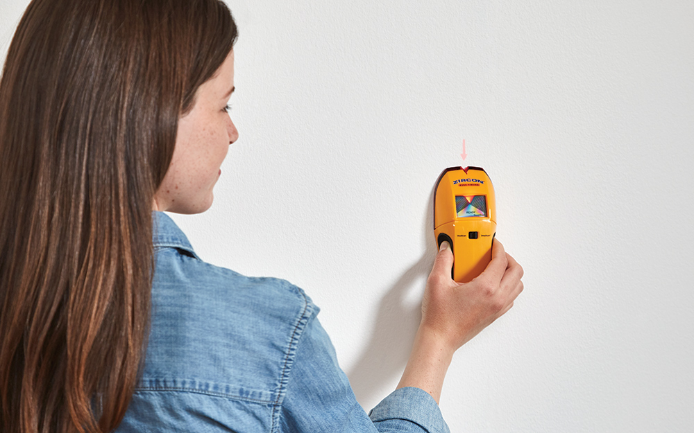 Woman using a stud finder on a wall.