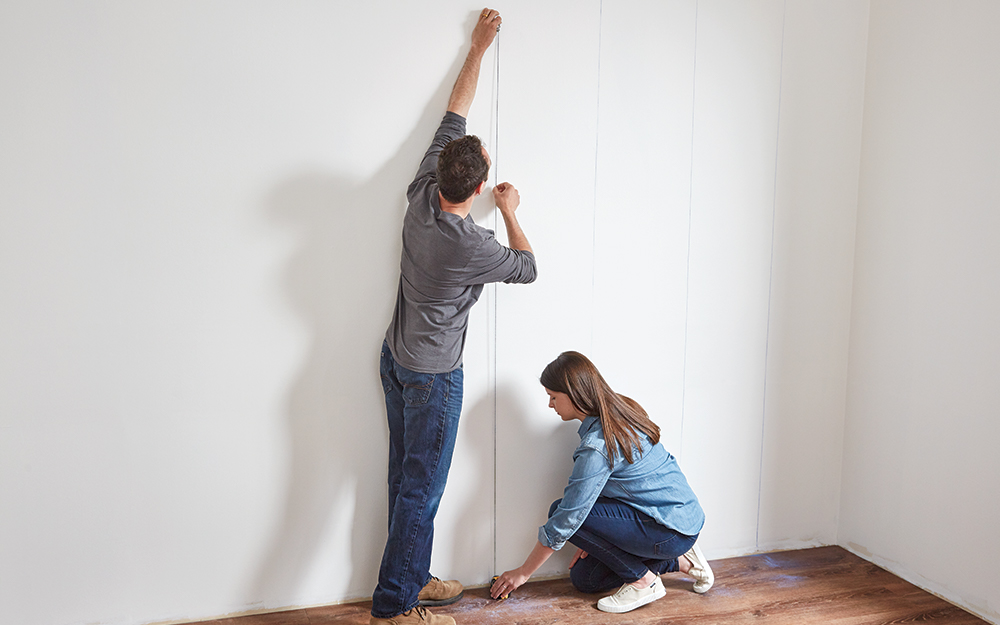 Couple adding a chalk line to a wall.