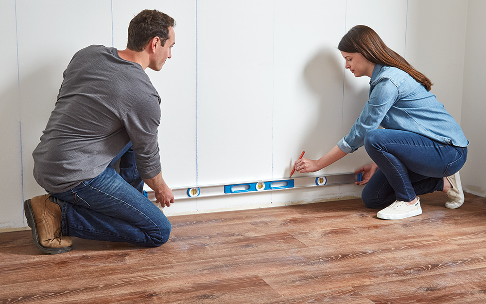 Couple marking a straight horizontal line using a level.