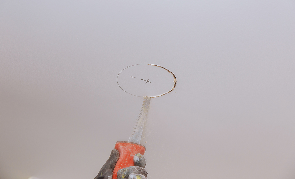 someone cutting a hole in a ceiling for a smoke alarm