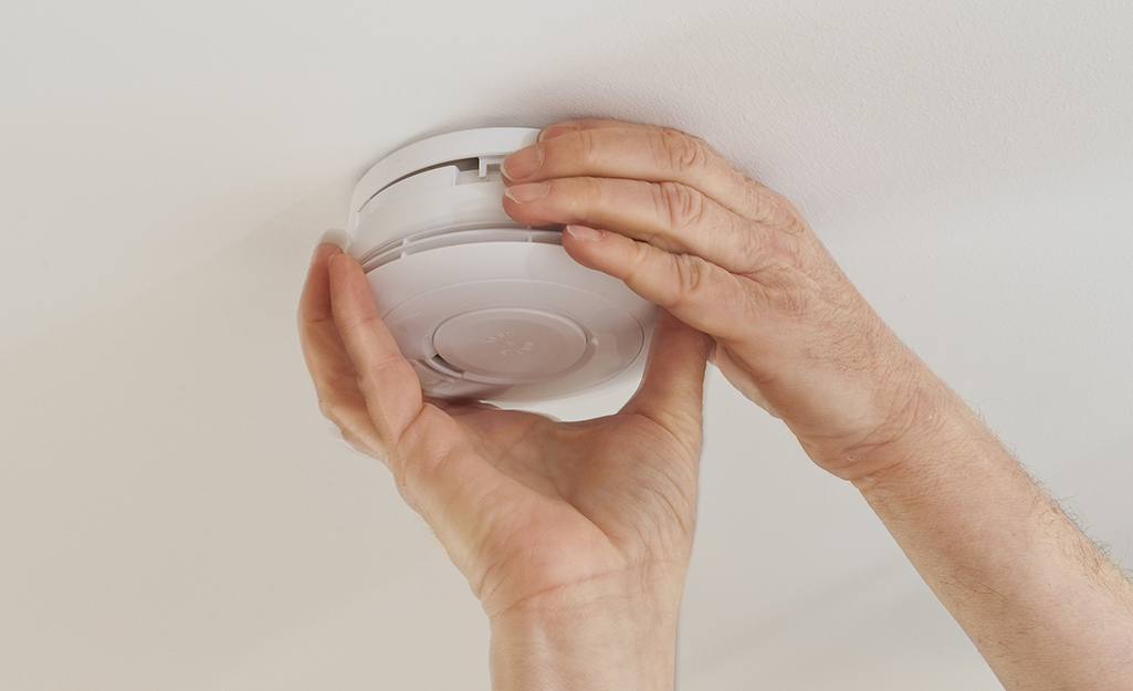 two hands attaching the mounting plate on a smoke alarm