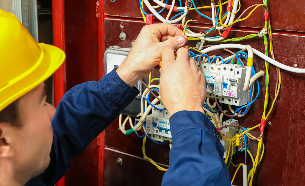 two hands wiring a smoke alarm