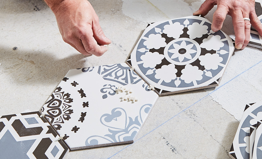 Person putting spacers between blue and white tiles.