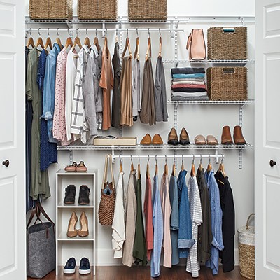 Clothes hanging on wire shelving in a closet.