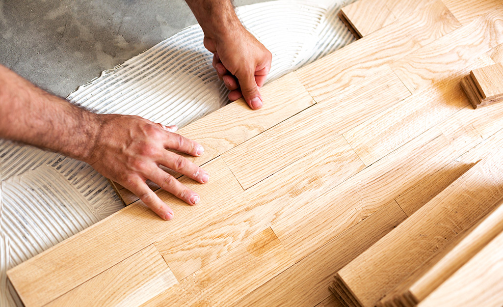 A person using floor adhesive to glue down hardwood flooring.