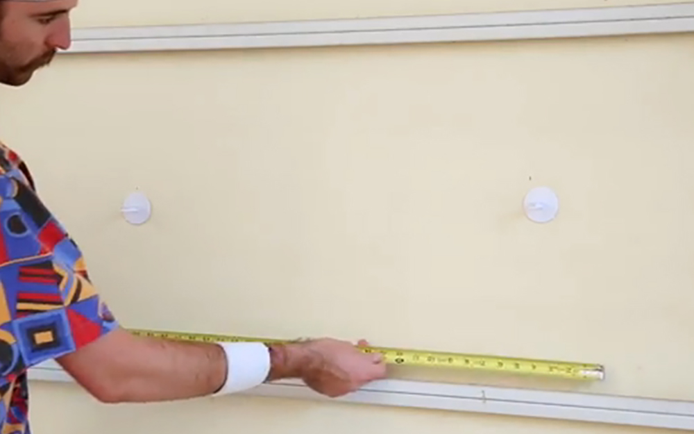 A man measuring door panels with a tape measure.
