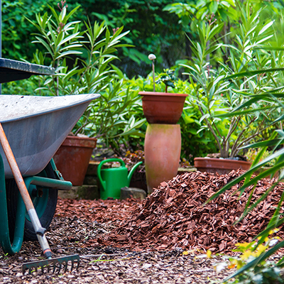 Garden tools by a pile of mulch