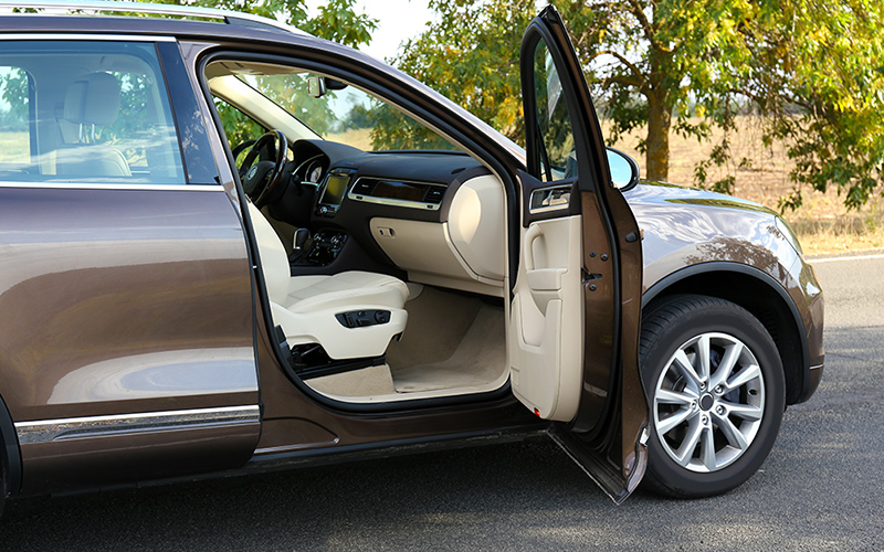 A brown car parked on a level surface with the door open.