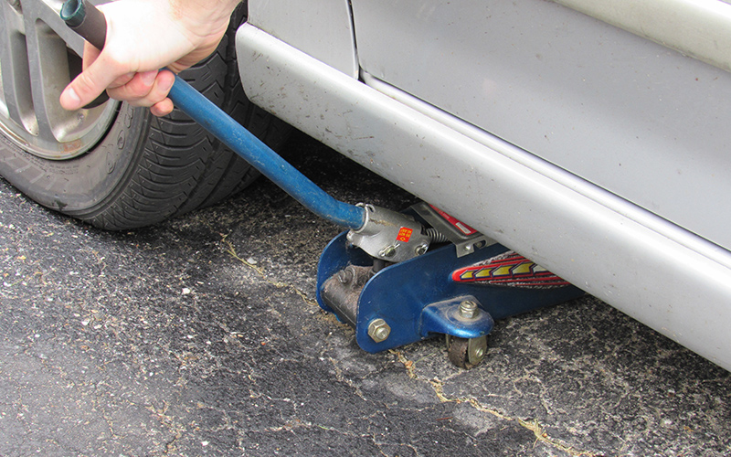 A person positioning a jack under a grey car.
