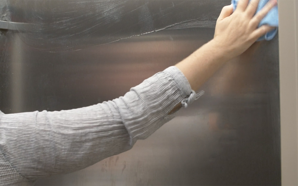 Person wiping the front surface of a stainless steel refrigerator.