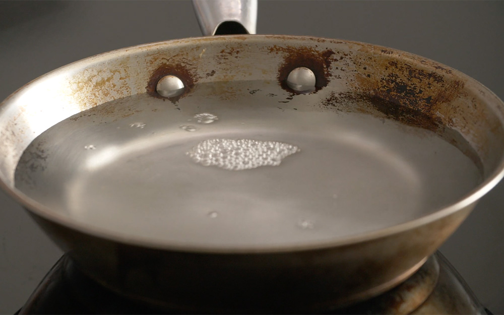 A set of stainless steel pans atop a stove with a stainless steel surface.