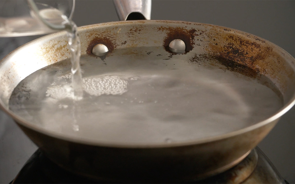 A stainless steel pan with water that is beginning to boil.