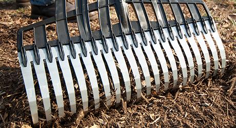 A large rake raking through soil.