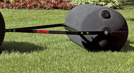 A roller pulled behind a mower pushing sod into the ground.