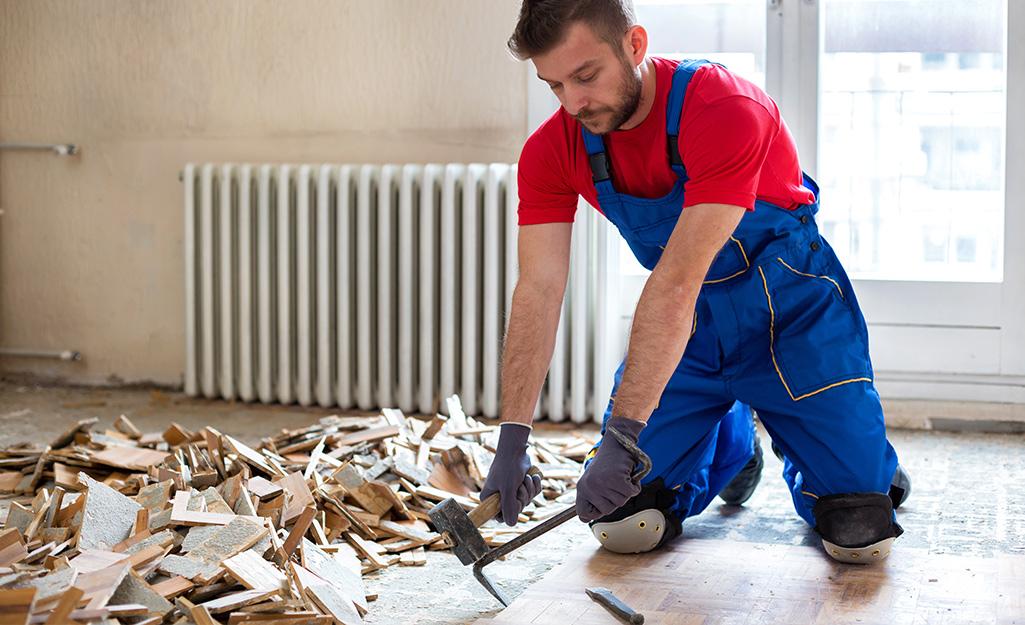 Một người đàn ông đeo găng tay lao động dùng búa để loại bỏ sàn nhà.