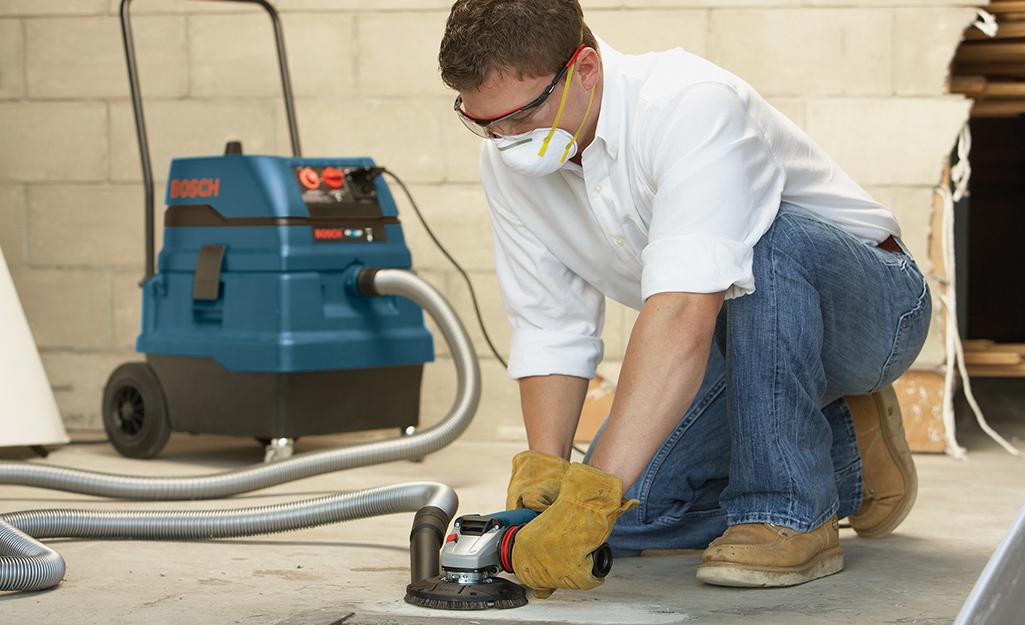 Một người đàn ông đeo khẩu trang và găng tay lao động dùng máy chà nhám để san phẳng sàn nhà.