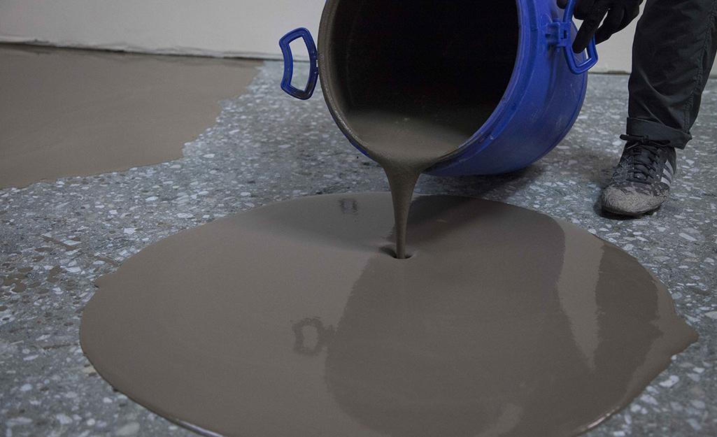 Có người đổ máy san sàn qua sàn để san bằng.