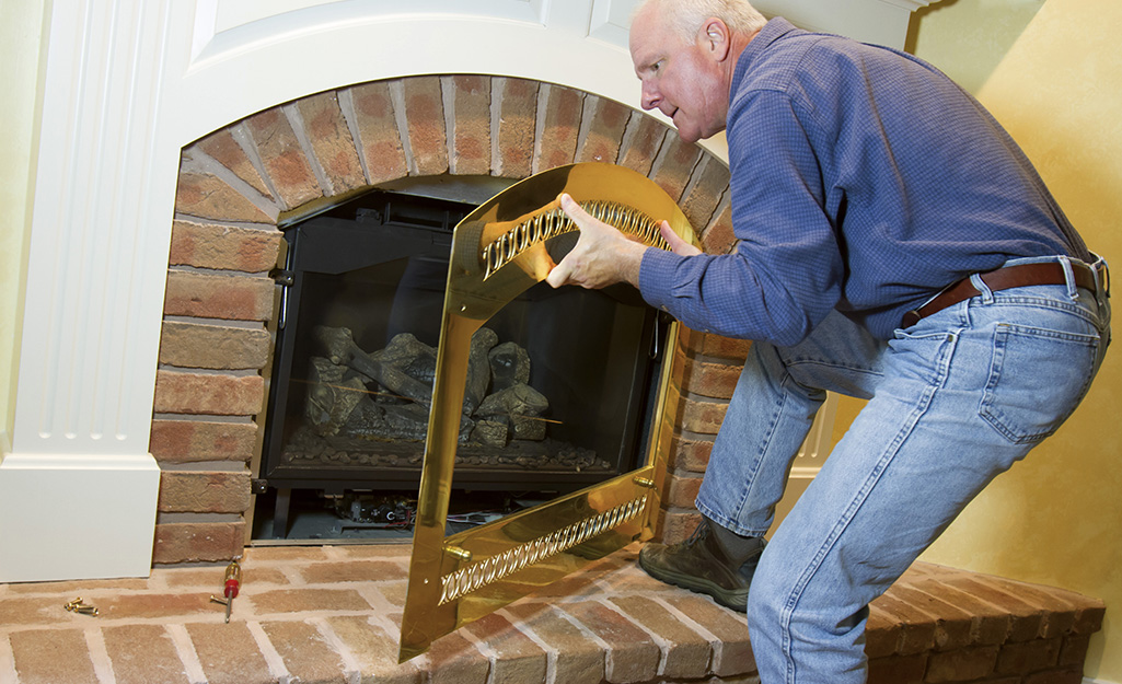 A person removes the glass screen from in front of a gas fireplace.