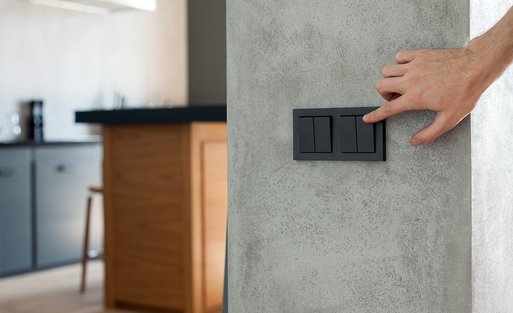 A person pushes a wall switch to control a gas fireplace.