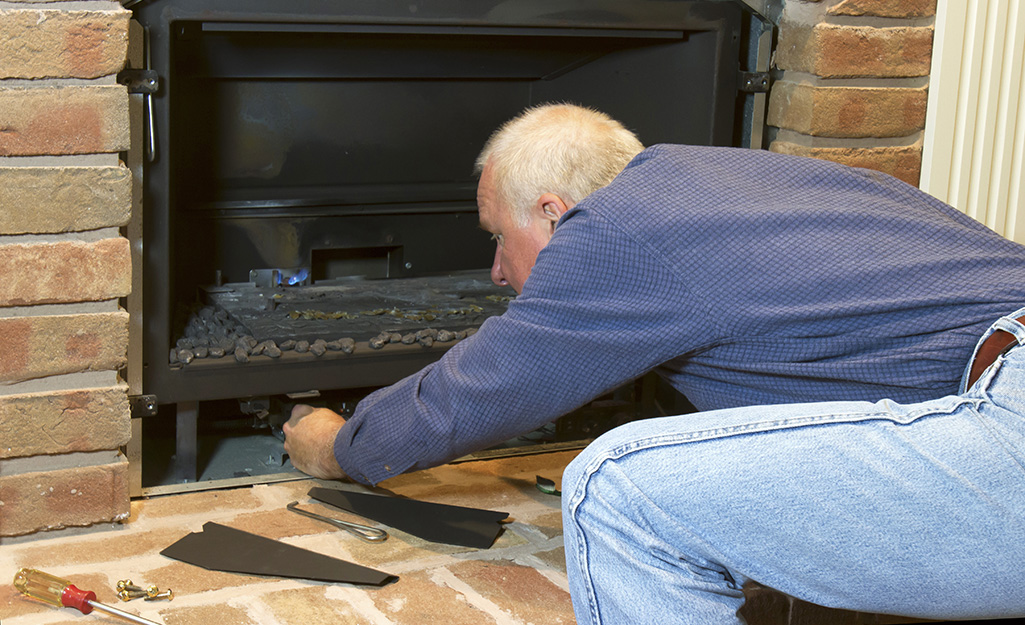 A person turns off a gas fireplace at the control panel.