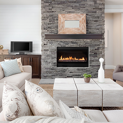 A gas fireplace inserted in a stone surround.