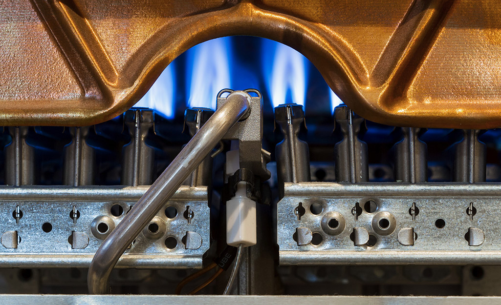 Gas burners are lit above the control mechanism of a water heater.