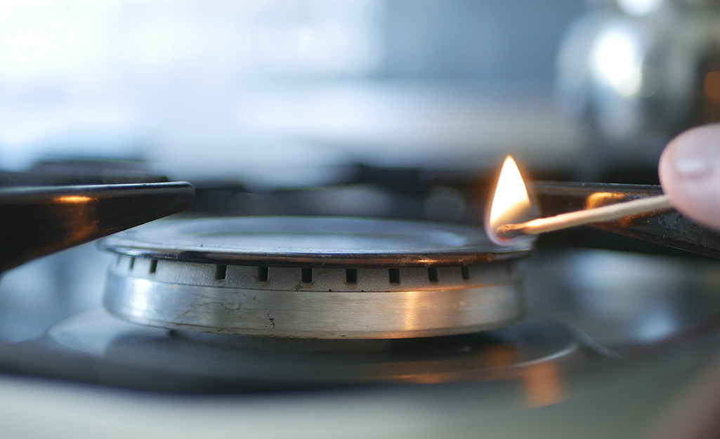 Someone lighting a burner on a gas stove top with a match.